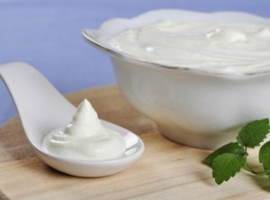 Sour cream in spoon on wooden cutting board. Small shallow DOF.